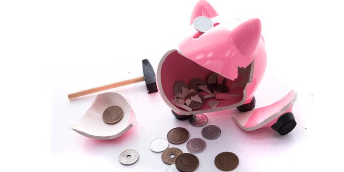 割れた豚の貯金箱とハンマー